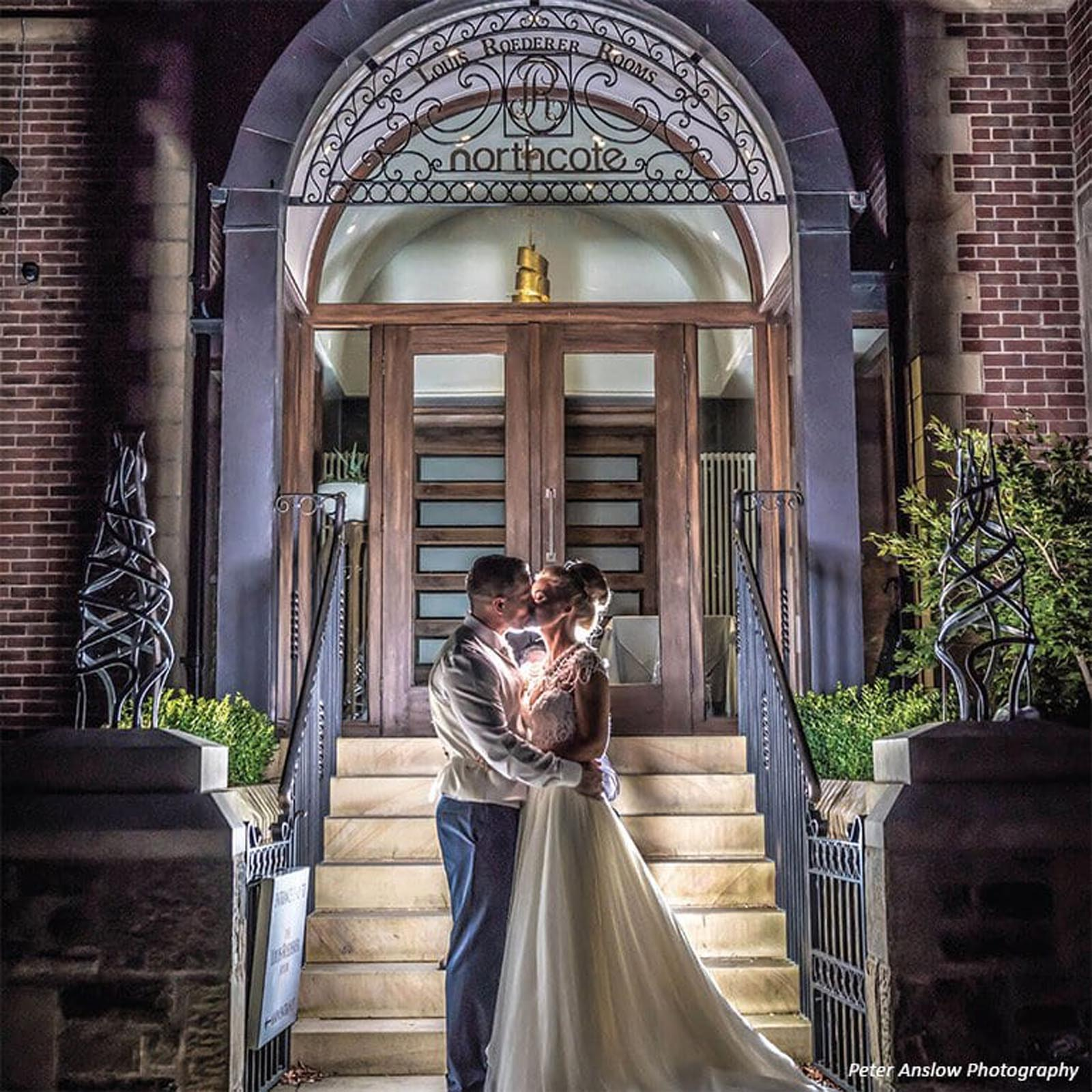 Bride and groom in front of Northcote