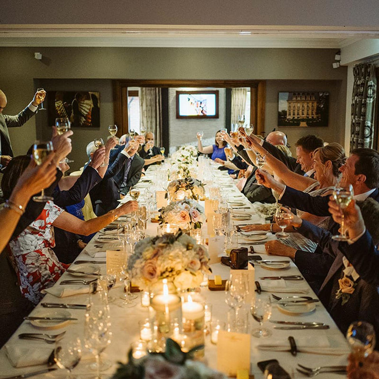 Guests all raising a glass in the private dining room.